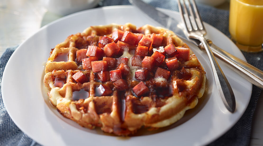 A waffle on a white plate topped with cubed SPAM and maple syrup