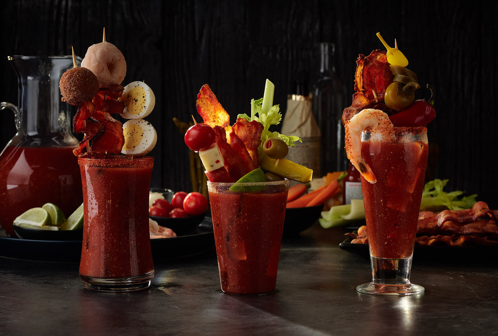 Three Bloody Mary cocktails on a tabletop