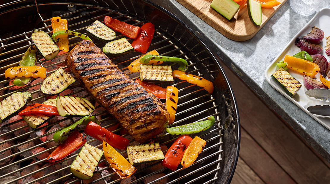 Pork Loin on a grill surrounded by various vegetables