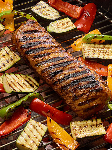 grilled pork loin and vegetables on a hot grill