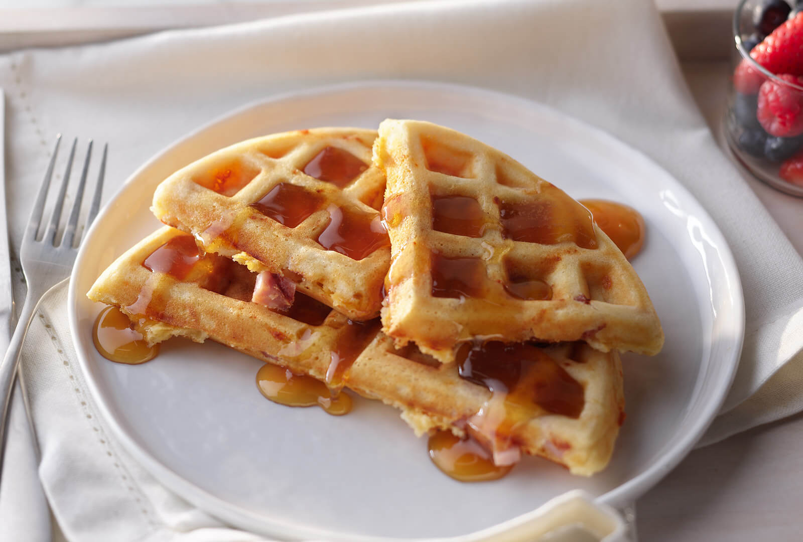 Savory Ham and Cheddar Waffles covered in maple syrup on a white plate