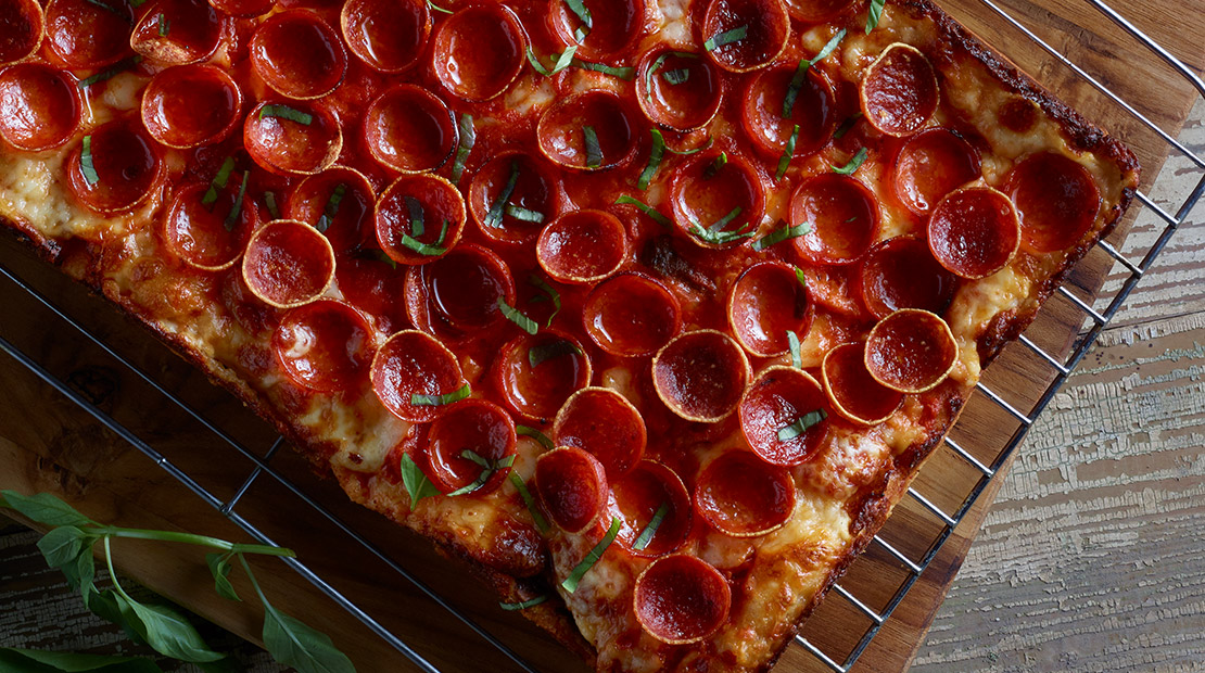 Detroit-style pizza with red curry tomato sauce, pepperoni and Thai basil