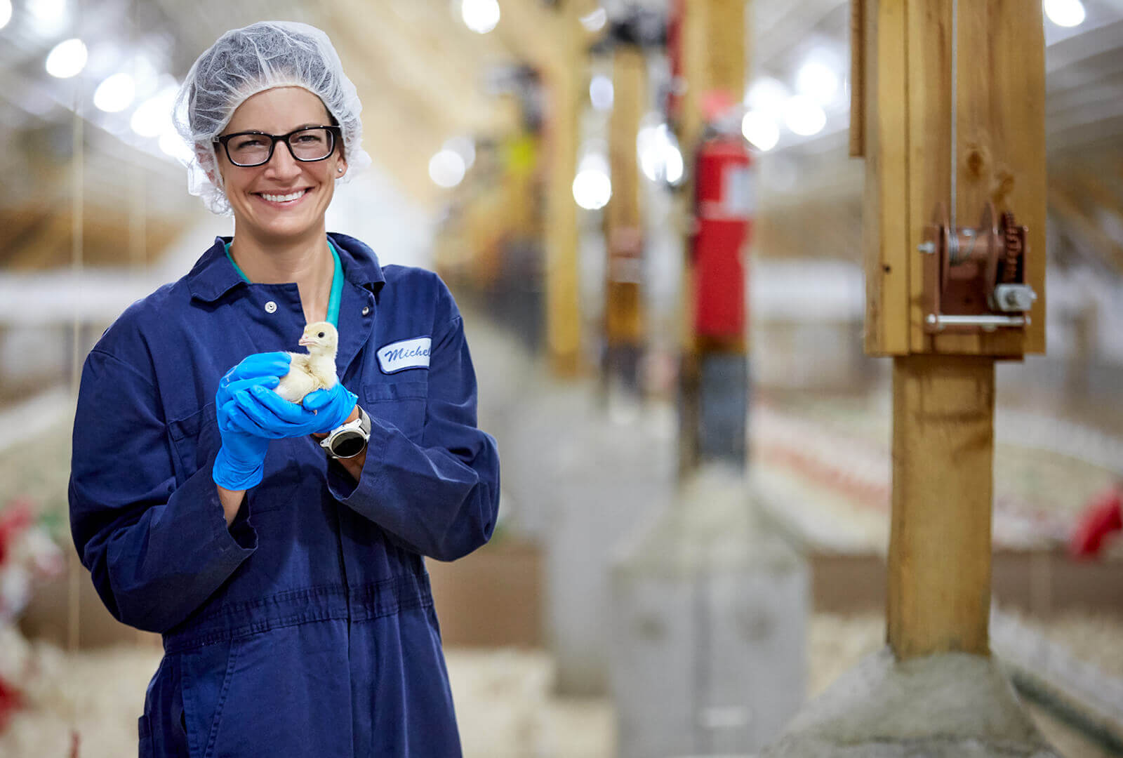 Woman holding turkey in barn
