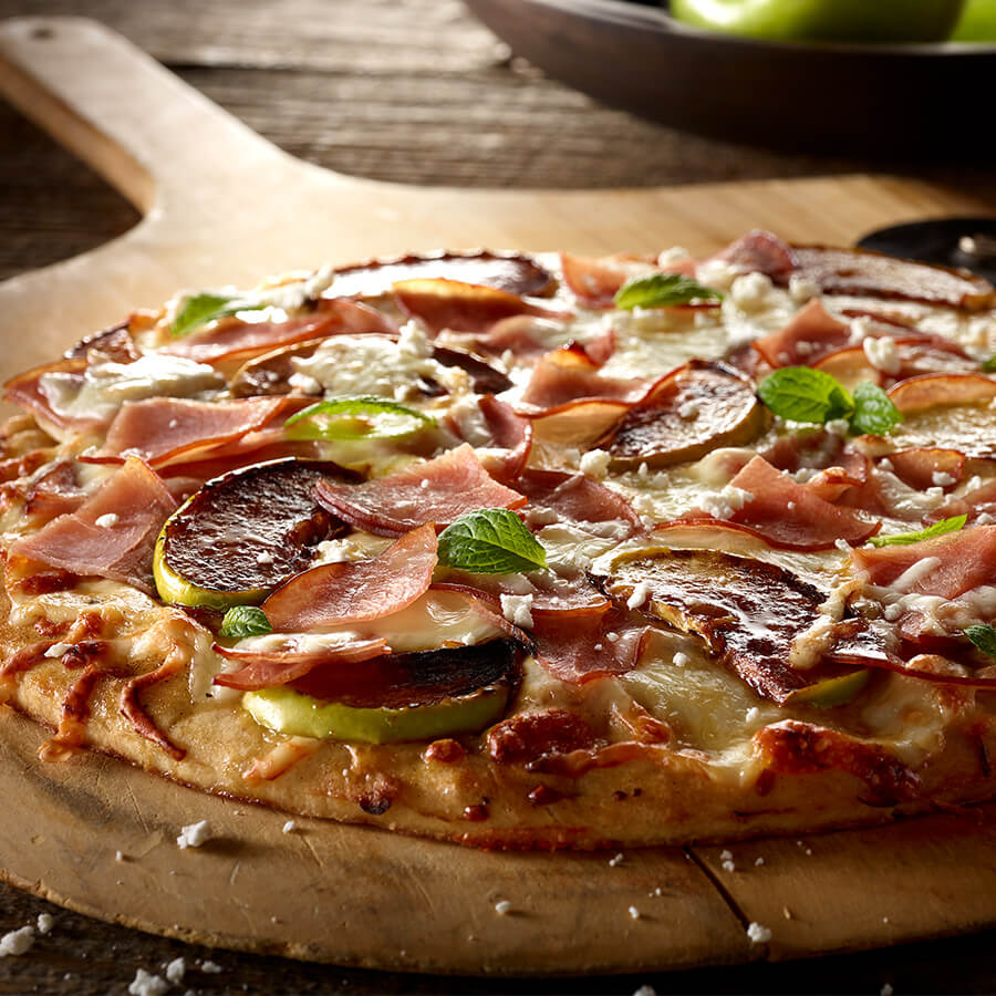 a pizza shot low to the survface, with apples, mint, and bacon