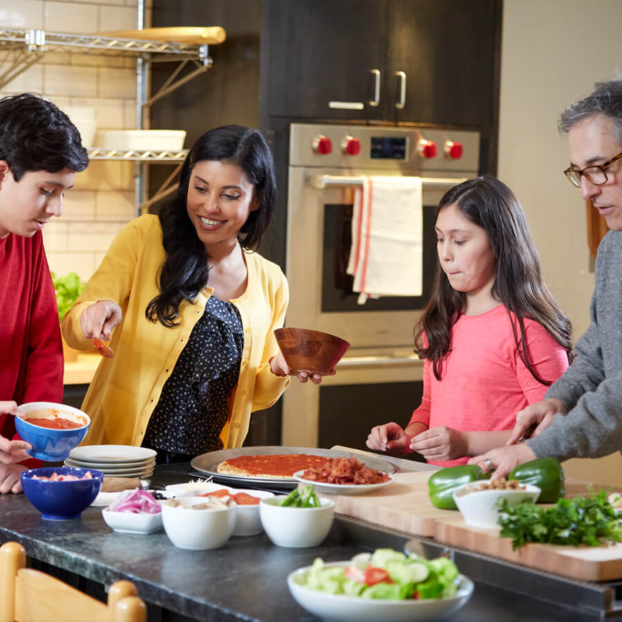 a hispanic family prepares a pizza dinner in their kitchen