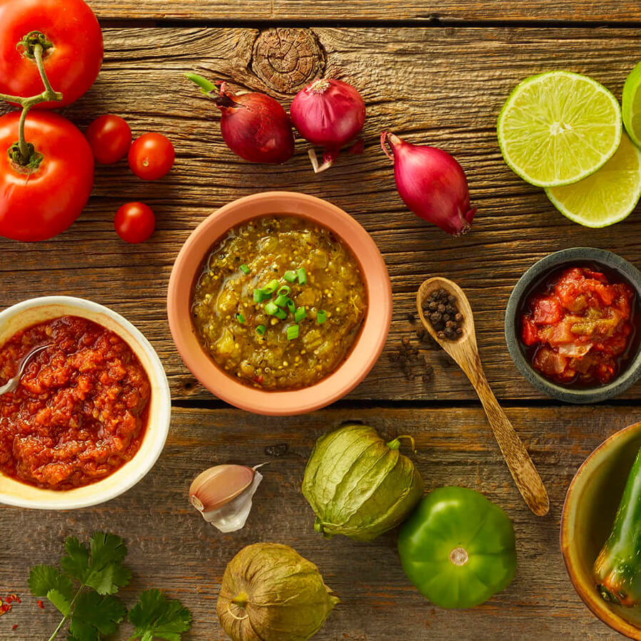 three small bowls with salsas in them, surrounded by whole ingredients