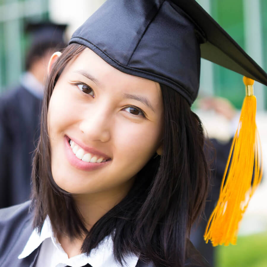 a closeup photo of a female student smiling in her cap and gown