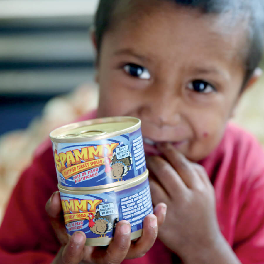 a Guatemalan child holds two cans of Spammy