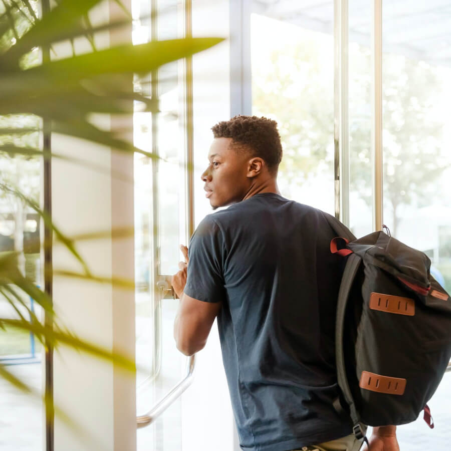 a male student with a backpack exiting a glass door