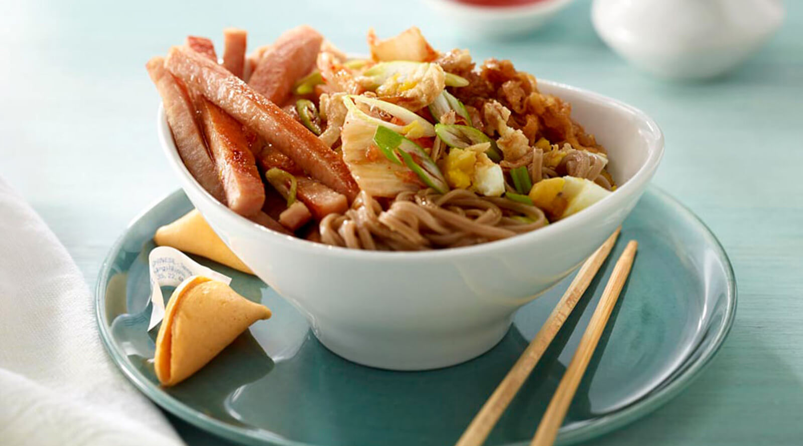 a bowl of asian noodles and sliced SPAM