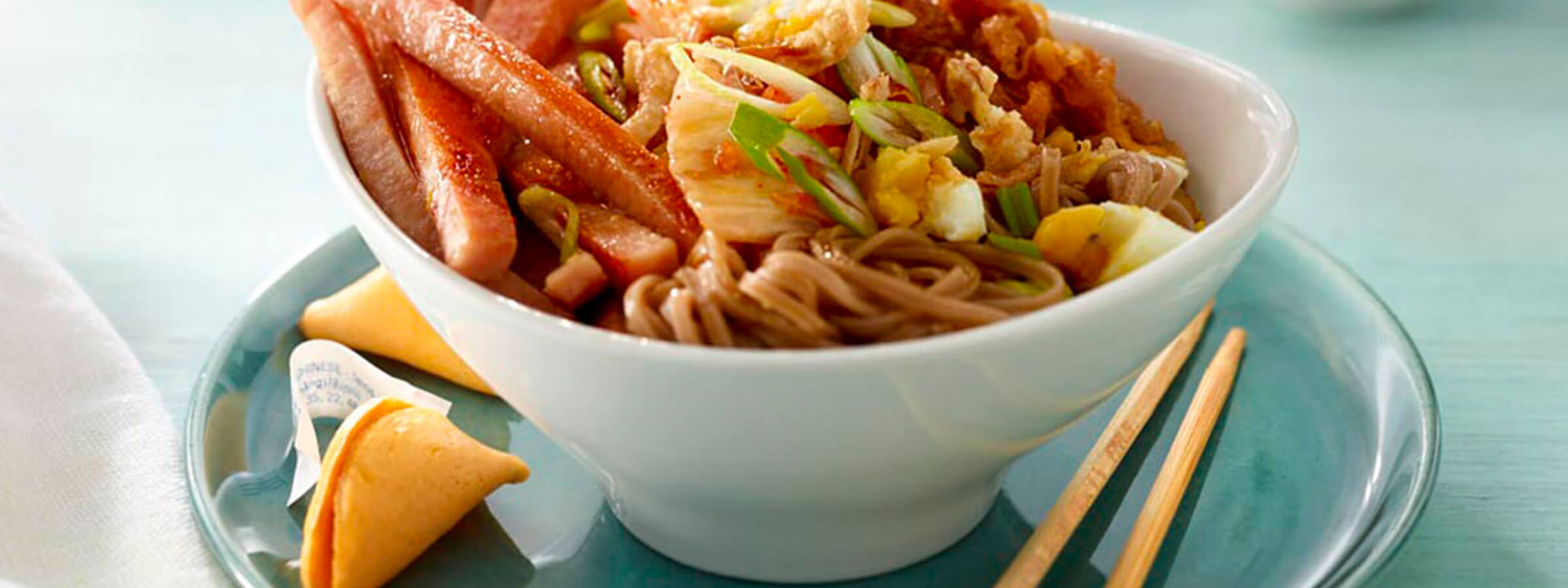 An asian bowl of noodles with Spam slices