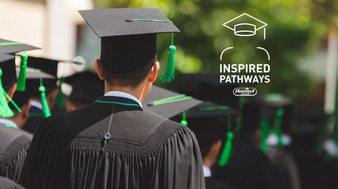 Inspired Pathways graduates walking outdoors with green tassels on mortarboard