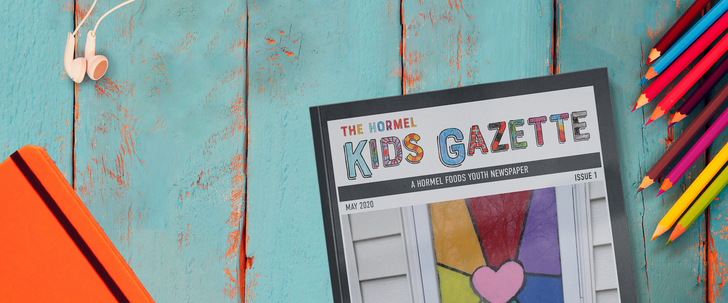 Hormel Kids Gazette on a blue table with art supplies