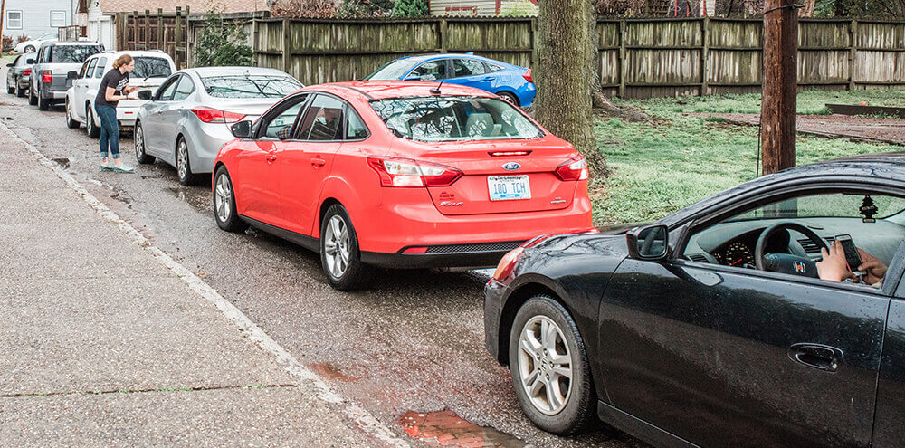 A line of cars waiting to receive to-go meals