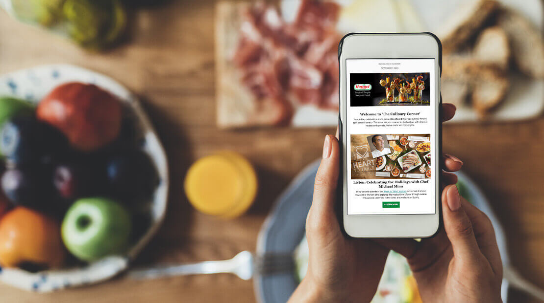 Person looking at Hormel Culinary newsletter on phone in kitchen