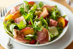 A plate of prosciutto, Arugula and pickled stone fruit salad