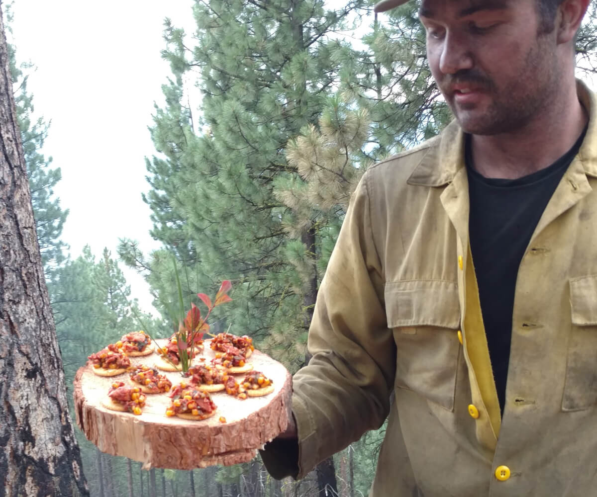 A firefighter holding a platter of some prepared SPAM in the woods