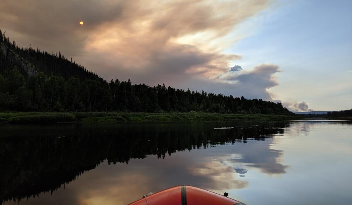 A kayak on a lake looking at a smokey sky